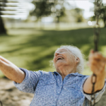 Cheerful senior woman on a swing at the park
