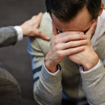 Image of a man grieving and a therapist