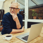 Senior man sitting outside drinking coffee and using a laptop