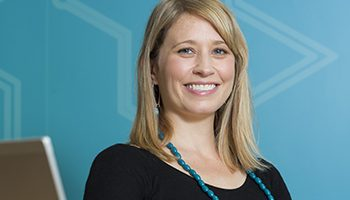Image of Dr Anna Kemp-Casey. She is wearing black and is standing in front of a blue wall at the Sax Institute.