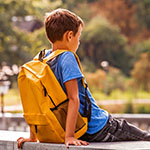 A boy sitting on a low concrete fence. He is facing away from the camera and wearing a yellow school back-pack.